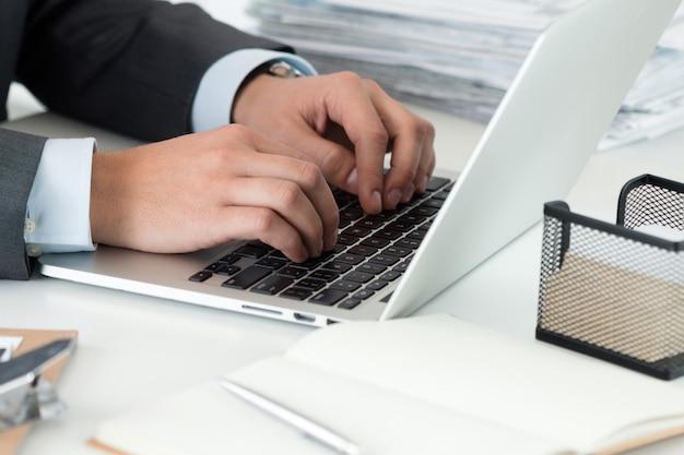 Zbliżenie: biznesmen ręce pracujące na komputerze. mężczyzna pisze coś siedzi w swoim biurze. planowanie finansowe, czytanie wiadomości, bankowość internetowa, edukacja na odległość lub koncepcja księgowości.