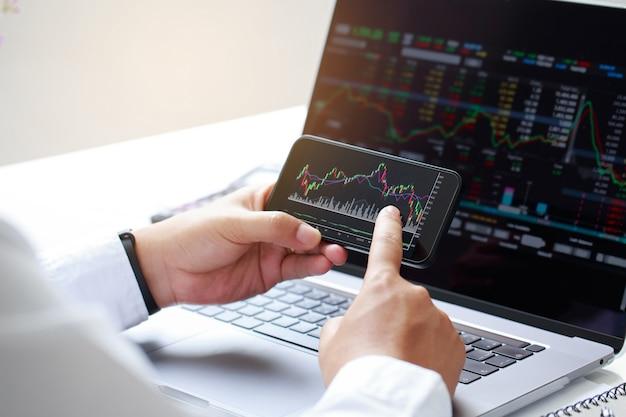 Zbliżenie biznesmen ręka trzymająca telefon i analiza wykres rynku finansowego giełda handlowa