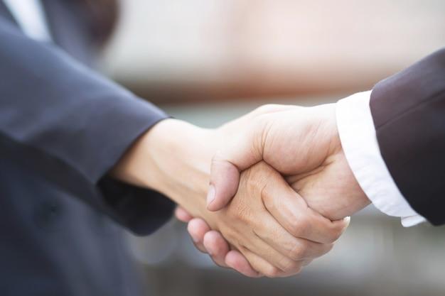 Zbliżenie biznesmen ręka wstrząsnąć bizneswoman między dwoma kolegami ok, odnieść sukces w biznesie trzymając się za ręce.