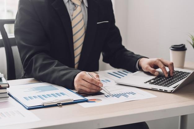 Zbliżenie biznesmen ręki trzymającej pióro wskazujące na wykres z laptopem w biurze.