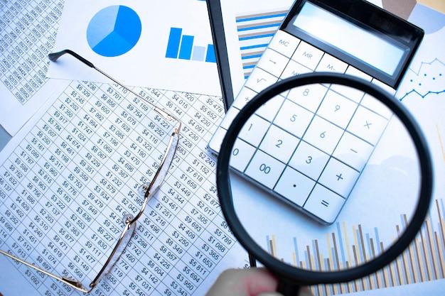 Zbliżenie: biznesmen sprawdzający rachunki za pomocą szkła powiększającego