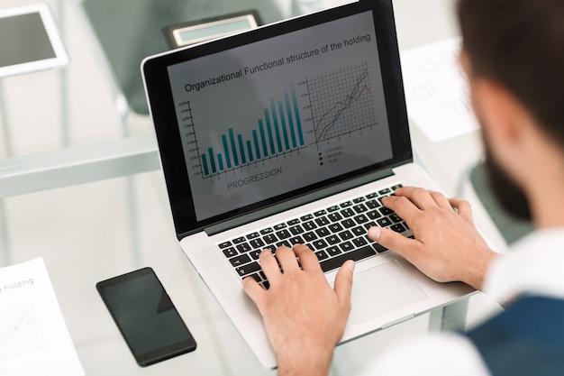 Zbliżenie biznesmen używa laptopa do pracy z danymi finansowymi