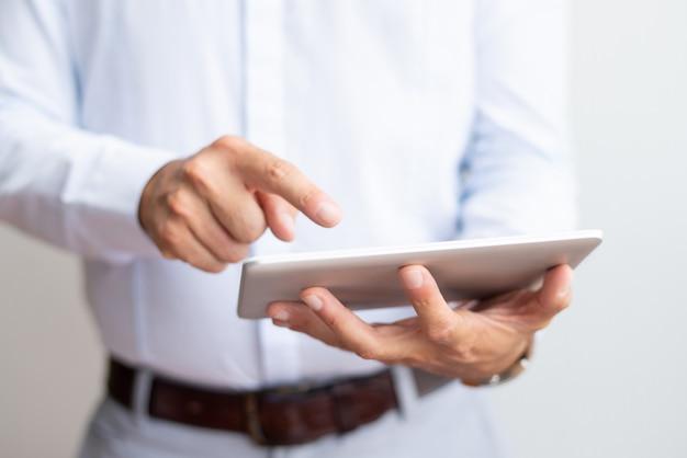Zbliżenie biznesmen używa pastylka komputer