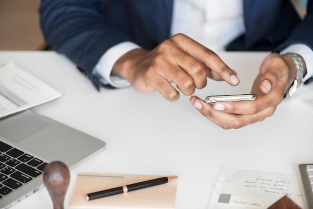 Zbliżenie biznesmen używa telefon komórkowego