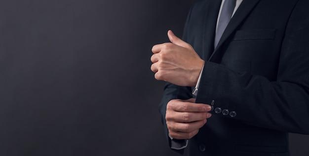 Zbliżenie biznesmen w czarnym garniturze i regulacji herbu, czarna ściana.