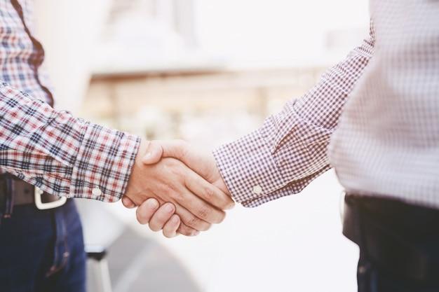 Zbliżenie biznesmen z bagażu podróży uścisk dłoni między dwoma kolegami pozdrawiam
