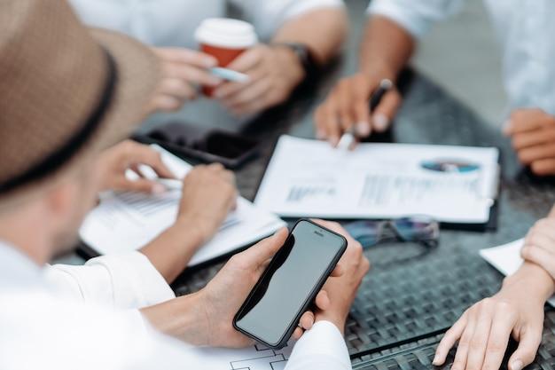 Zbliżenie. biznesmen za pomocą smartfona podczas spotkania w biurze. ludzie i technologie.