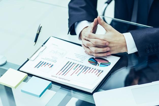 Zbliżenie biznesmen zastanawia się nad polityką finansową firmy siedzącej za biurkiem w biurze