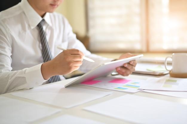 Zbliżenie biznesmena analizy dane w cyfrowej pastylce na biurowym biurku.