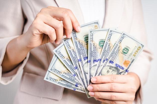 Zbliżenie biznesowa kobieta wręcza odliczającego pieniądze my dolarowi rachunki na bielu. koncepcja pieniądza.