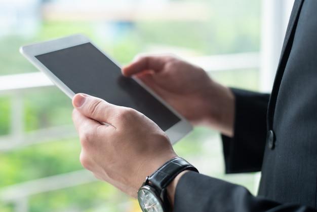 Zbliżenie biznesowa osoba używa pastylka komputer przy okno
