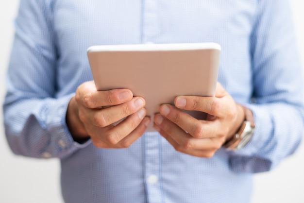 Zbliżenie biznesowego mężczyzna mienia pastylki komputer