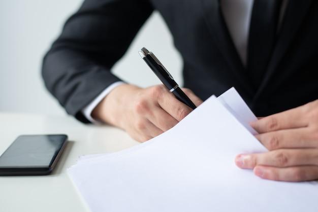 Zbliżenie biznesowego mężczyzna podpisywania dokument przy biurowym biurkiem
