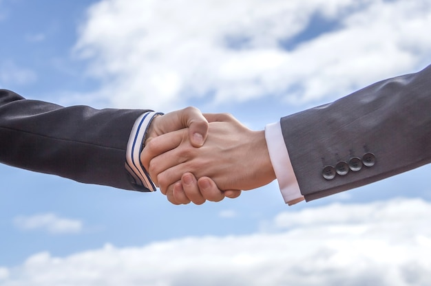 Zbliżenie biznesowego uścisku dłoni na tle błękitnego nieba