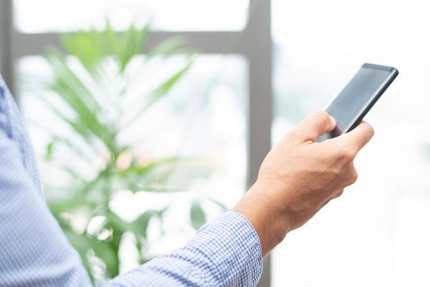 Zbliżenie biznesowej osoby klapanie na smartphone ekranie
