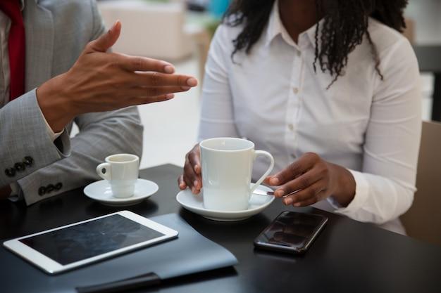 Zbliżenie biznesowi koledzy dyskutuje prac zagadnienia