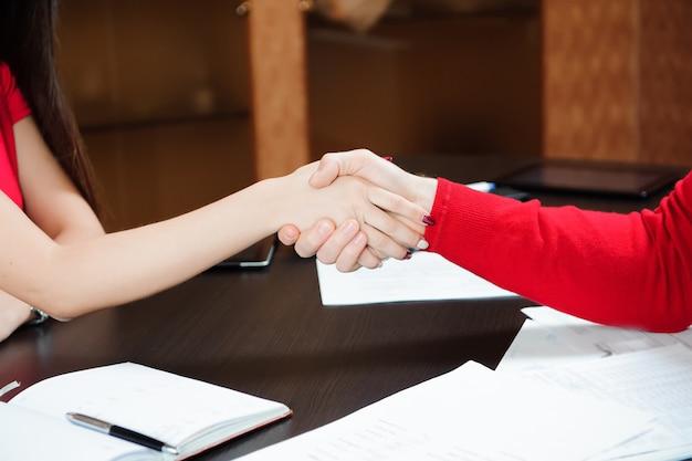 Zbliżenie biznesowy uścisk dłoni na tle stół z papierami