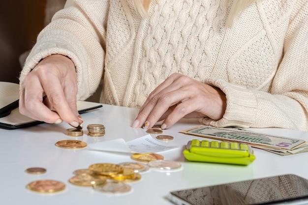 Zbliżenie bizneswoman liczy monety na stole, koncepcja oszczędzania pieniędzy, gospodarka, inwestycje