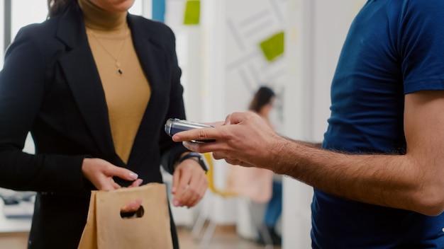 Zbliżenie bizneswoman płacącej zamówienie żywności z płatnością zbliżeniową za pomocą inteligentnego zegarka