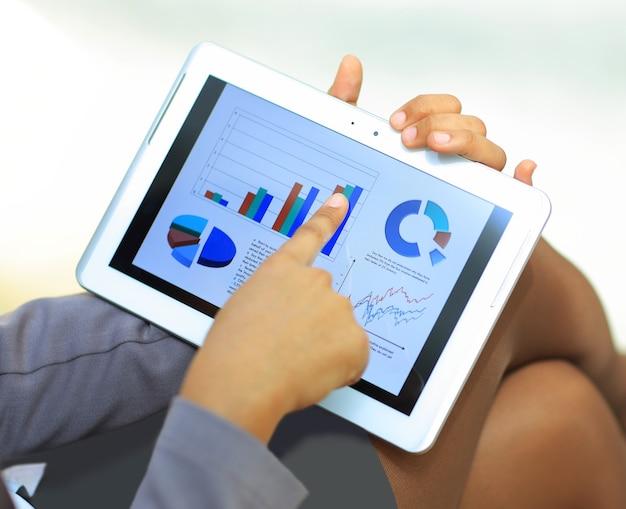 Zbliżenie: bizneswoman przy użyciu komputera typu tablet do pracy z danymi finansowymi