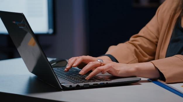 Zbliżenie: bizneswoman ręce na klawiaturze, siedząc przy biurku w biurze firmy startowej planowania projektu gospodarczego w internecie. menedżer wykonawczy wpisujący statystyki finansowe w odpowiedzi na e-maile biznesowe