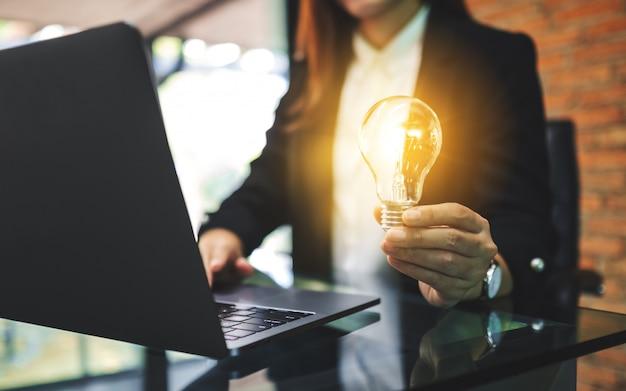 Zbliżenie bizneswoman trzyma rozjarzoną żarówkę podczas gdy pracujący na laptopie w biurze