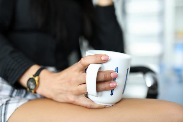 Zbliżenie: bizneswoman w ubranie siedzi na krześle w biurze. kobieta relaks po męczącym dniu. osoba płci żeńskiej śniadanie. koncepcja porannej kawy