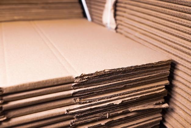 Zbliżenie boków stosów tektury złożonych jeden na drugim. koncepcyjne przechowywanie pudełek z przyjaznego dla środowiska i odnawialnego materiału.