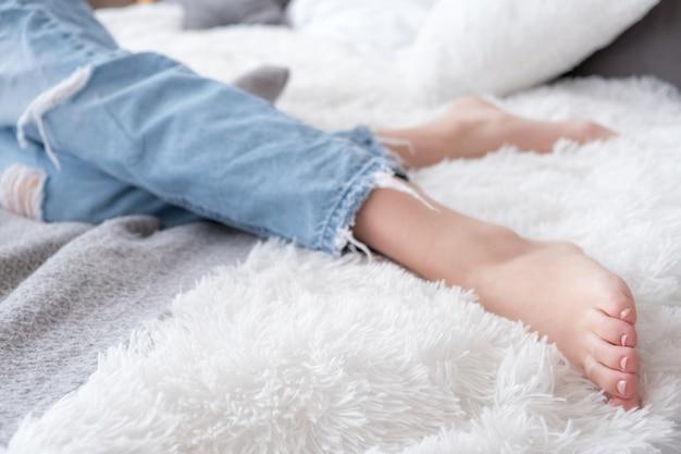 Zbliżenie boso atrakcyjne kobiece nogi ubrane w niebieskie dżinsy w łóżku, dom relaks i odpoczynek