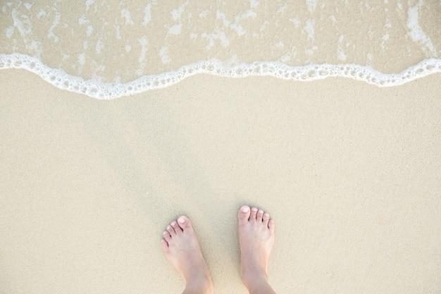 Zbliżenie bosych stóp mężczyzny stojących na mokrej plaży, z delikatnie piaskową krawędzią pod nimi. wakacje na plaży nad oceanem, spacer po morskim piasku.
