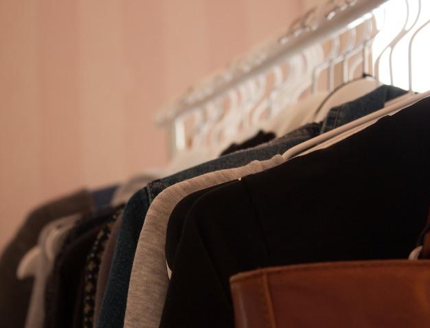 Zbliżenie brązowa skórzana torba i ubrania wieszane na białych wieszakach