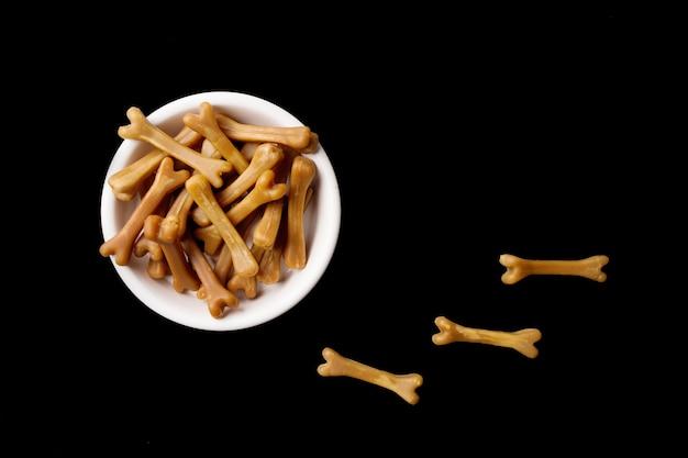 Zbliżenie: brązowe kości karmy dla psów w misce białego psa na czarnym tle. zdjęcie wysokiej jakości