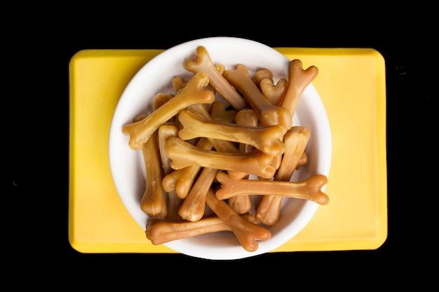 Zbliżenie: brązowe kości karmy dla psów w misce białego psa na czarnym tle. żółty uchwyt na miskę. zdjęcie wysokiej jakości