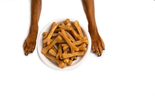 Zbliżenie: brązowe kości karmy dla psów, w misce z białym jedzeniem, na tle białego studia. brązowe łapy szczeniaka. zdjęcie wysokiej jakości