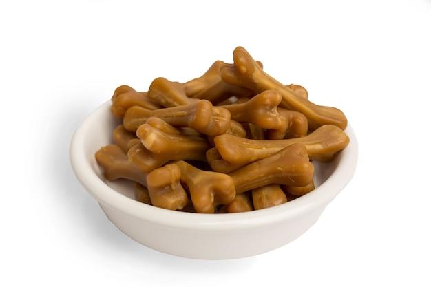 Zbliżenie: brązowe kości karmy dla psów, w misce z białym jedzeniem, na tle białego studia. zdjęcie wysokiej jakości
