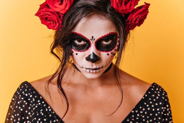 Zbliżenie brązowookiej kobiety z karnawałową sztuką twarzy. meksykański model jest zły, patrząc na kamery na pomarańczowym tle.