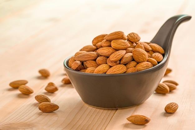 Zbliżenie brązowy świeży migdały nasion w misce kształt czarnej łyżki na drewnianym stole.
