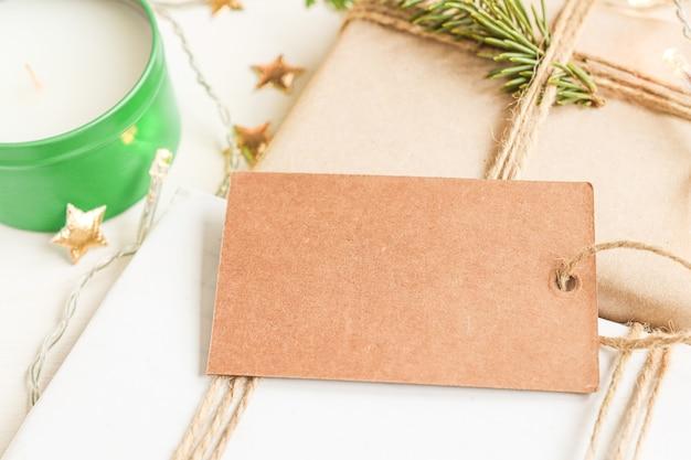Zbliżenie brązowy tag na miejsce na kopię na świątecznym tle z dekoracjami świątecznymi i noworocznymi