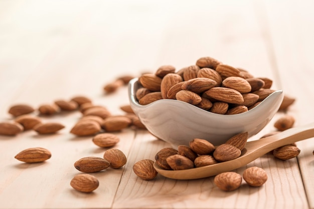 Zbliżenie brązowych nasion świeżych migdałów w białej misce i drewnianą łyżką na drewnianym stole.