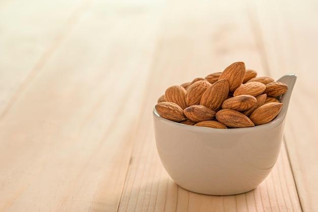 Zbliżenie brązowych nasion świeżych migdałów w białej misce na drewnianym stole.