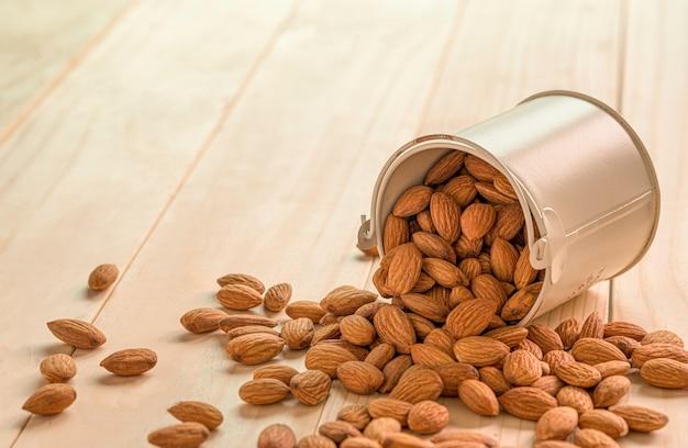 Zbliżenie brązowych nasion świeżych migdałów w starym aluminiowym wiadrze na drewnianym stole.
