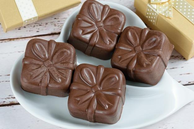 Zbliżenie brazylijskie ciastka miodowe na talerzu w kształcie serca, w otoczeniu złotych pudełek na prezenty.