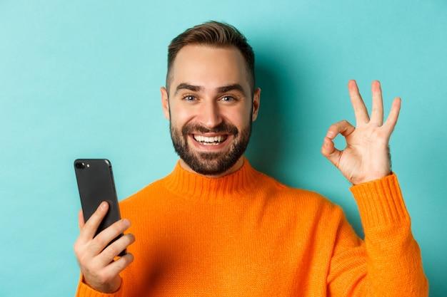 Zbliżenie: brodaty mężczyzna trzymający smartfon i pokazujący znak w porządku, polecający aplikację mobilną, stojący zadowolony na turkusowym tle.