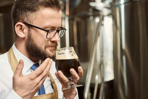 Zbliżenie brodaty mężczyzna w okularach pachnące smaczne ciemne piwo po warzenia. profesjonalny piwowar męski degustuje piwo i bada jakość trunku. pojęcie produkcji i rzemiosła.