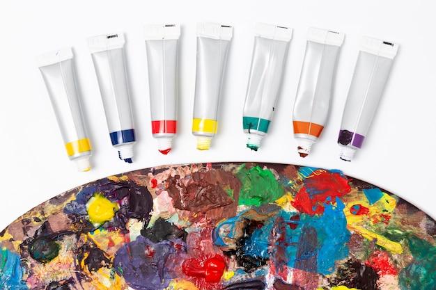 Zbliżenie brudnej palety kolorów i rur akwarelowych