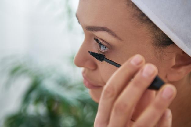 Zbliżenie brunetka kobieta nakładająca tusz do rzęs na jej rzęsy. koncepcja makijażu