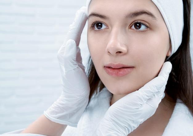 Zbliżenie brunetka z czystą skórą patrzeje lekarkę w piękno salonie