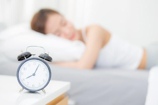 Zbliżenie budzik i piękna azjatykcia młoda kobieta w ranku.