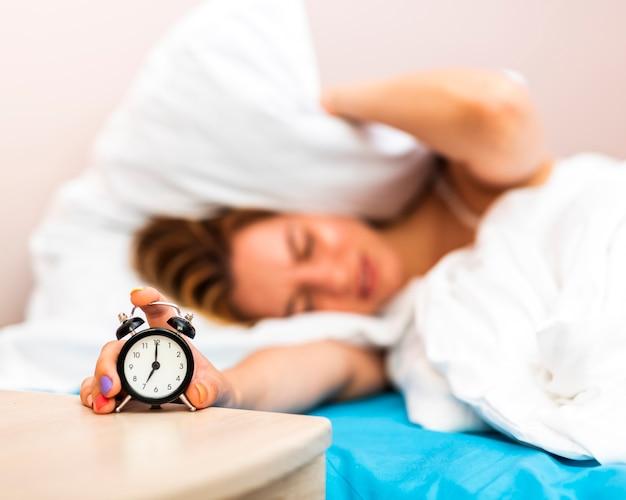 Zbliżenie budzik zatrzymany przez śpiącą kobietę