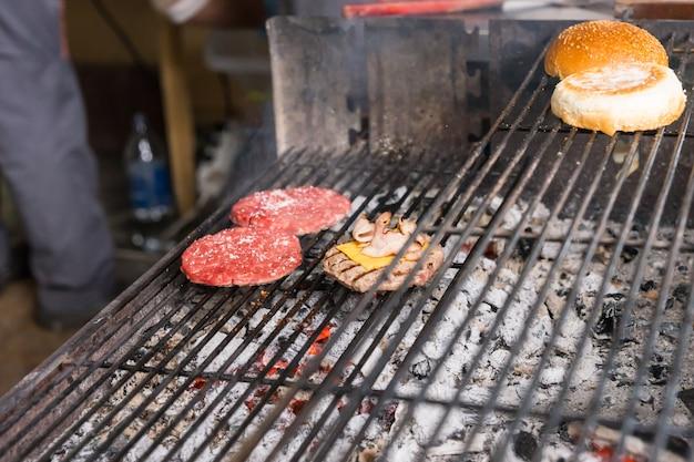 Zbliżenie burger patties gotowanie na gorącym grillu na węgiel drzewny z opiekaniem bułek na górnym ruszcie